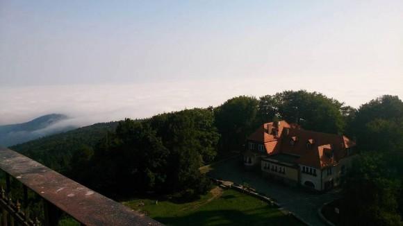 widok z wieży kościelnej na Dom Turysty PTTK im. Romana Zmorskiego, z 1908 r. i morze mgieł