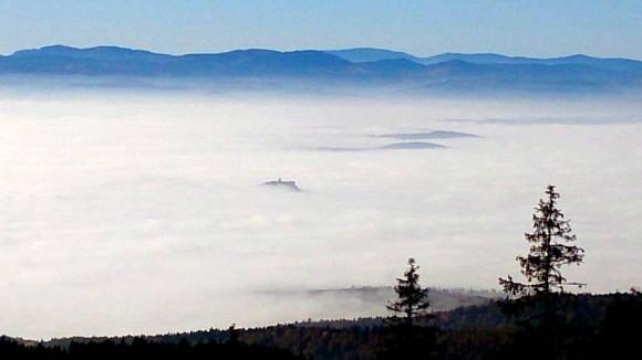 ruiny zamku i morze szczytów we mgle