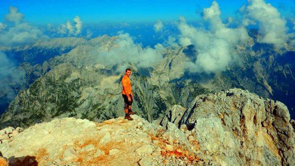 autor na szczycie Triglava z panoramą Alp Julijskich